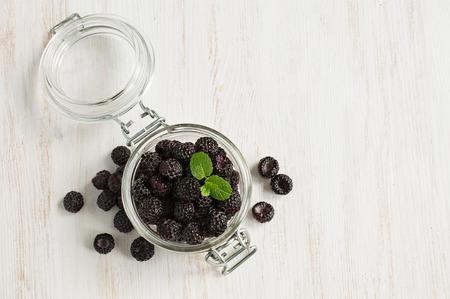 black raspberries: Black raspberries in a glass jar on a white wooden background