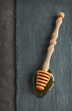 dipper: Wooden dipper with honey on slate background