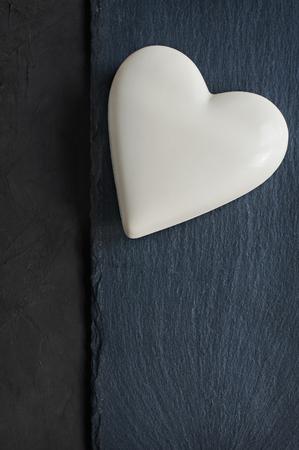 黒いスレートの背景にホワイト チョコレート ハート