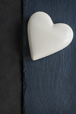 White chocolate heart on black slate background 版權商用圖片