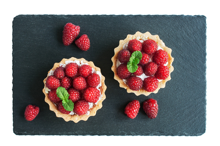 Tartlets with raspberries on a slate board