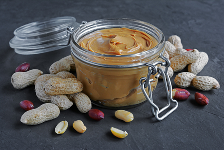 Peanut butter in a glass jar and peanuts on a black slate background