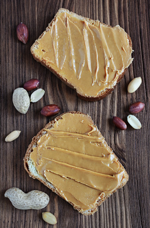 Peanut butter on a slice of toast on a wooden background Stock Photo