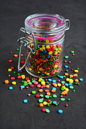 sprinkling: Colorful confectionery sprinkling, decoration for cake and bakery in a glass jar on black background