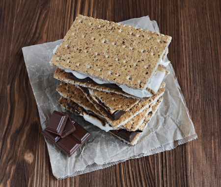 Graham: Fresh homemade smores with marshmallows, chocolate and graham crackers on wooden table. The popular American cuisine dessert. Stock Photo
