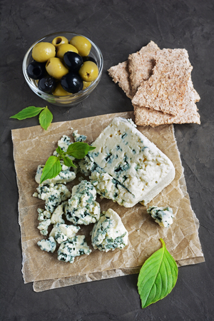 stilton: Blue cheese with olive, basil and crispbread on black background