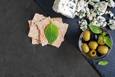 stilton: Blue cheese with olive, basil and crispbread on black slate board