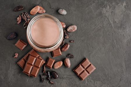 Chocolate milk with pieces of chocolate bar and cacao beans on black concrete background 스톡 콘텐츠