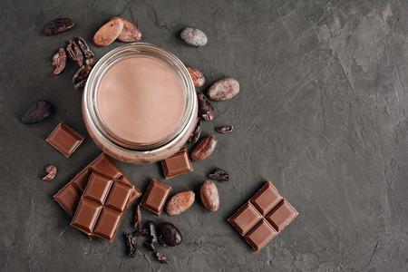 Chocolat au lait avec des morceaux de chocolat et des haricots de cacao sur fond de béton noir