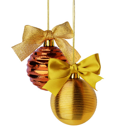 Golden Christmas balls with ribbon bows hanging over white background