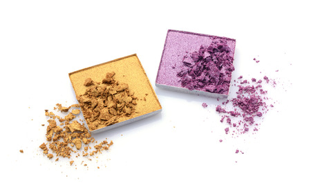 Crushed golden and violet eyeshadows isolated on white Stock Photo