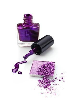 Violet eyeshadow and nail polish isolated on white