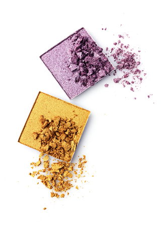 Crushed golden and violet eye shadow isolated on white