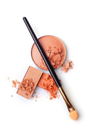 Beige and orange crushed eyeshadow and makeup brush isolated on white background Stock Photo