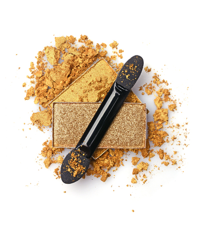 Crushed golden eyeshadow and applicator isolated on white background
