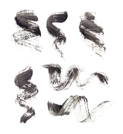 Collection of smears of black mascara on isolated white background