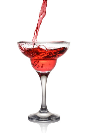 Splash in glass of a pink alcoholic cocktail drink isolated on white background