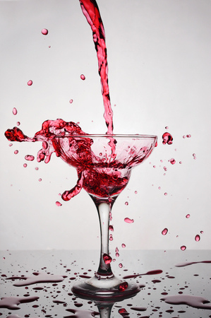 Splash in glass of a pink alcoholic cocktail drink on gradient background