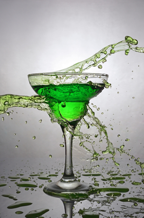 gray gradient reflection: Splash in glass of green alcoholic cocktail drink on gray gradient background
