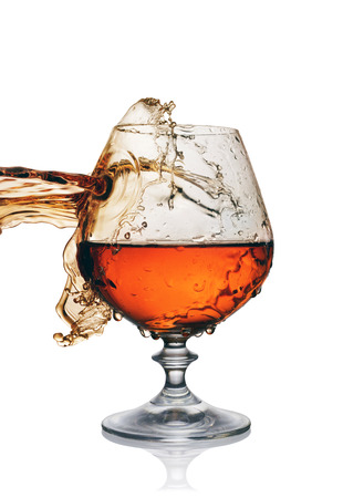 Splash in glass of cognac isolated on white background