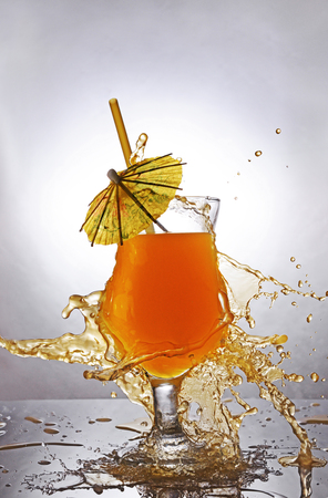 Splash in glass of orange alcoholic tropical cocktail drink with umbrella and straw on gray gradient background