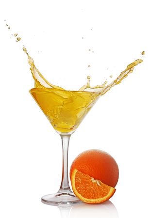 Splash in glass of yellow alcoholic cocktail drink with orange isolated on white background