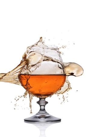 Splash in glas Cognac geïsoleerd op een witte achtergrond Stockfoto