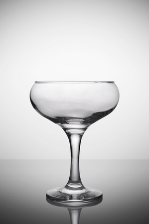 Empty glass for champagne sparkling wine on gray gradient background