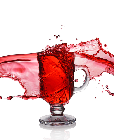 Splash in glass of mulled wine isolated on white background