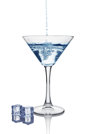 Blue splash in glass of white transparent alcoholic cocktail drink with ice cube isolated on white background Stock Photo