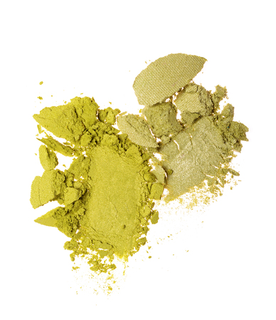 Smears of two crushed green eyeshadow as sample of cosmetic product isolated on white background