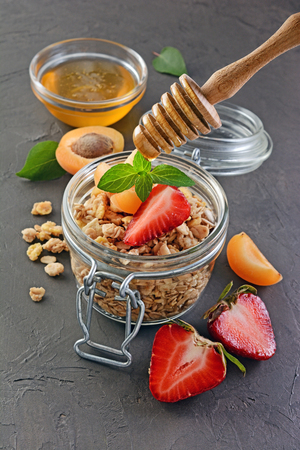 wholegrain: Healthy breakfast. Homemade granola in glass jar with fresh strawberry, apricot, honey and mint on black background Stock Photo