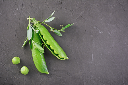 Healthy food. Fresh green peas with leaves on black background