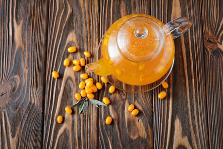 Glass teapot of hot vitaminic healthy sea buckthorn tea with fresh raw yellow berries on wooden background