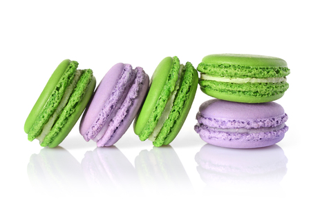 French dessert. Sweet green and purple macaroons or macarons isolated on white background
