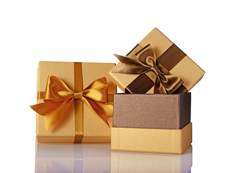 Two golden classic shiny gift boxes with brown satin bows isolated on white background Stock Photo