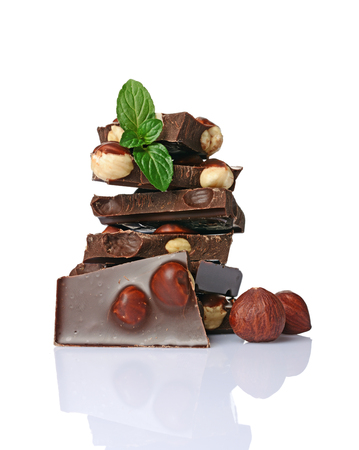 Close-up pieces of black chocolate bar with whole hazelnuts and mint isolated on white background