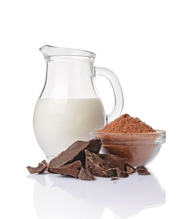 Close-up pieces of chunk black chocolate with glass bowl of cocoa powder and jug of milk isolated on white background 스톡 콘텐츠