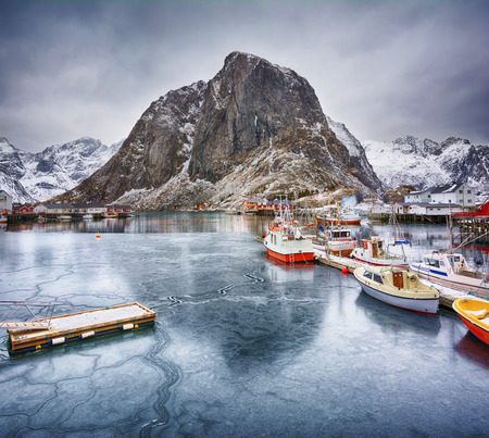 Beautiful winter landscape of picturesque harbor with fishing boats and traditional Norwegian rorbus in Lofoten islands, Norway