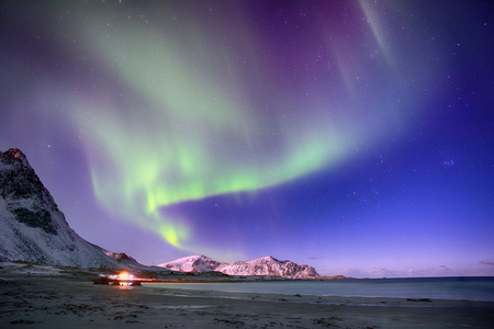 Polar lights in the sky above the mountains on the northern beach of Lofoten islands in the Norwegian Sea