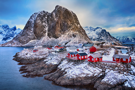 Beautiful winter landscape of picturesque fishing village with red rorbu in the mountains of Lofoten islands in Norwegian Sea, Norway Stock Photo