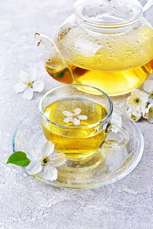 Close-up glass teapot and teacup with green tea and spring flowers on gray concrete background Stok Fotoğraf