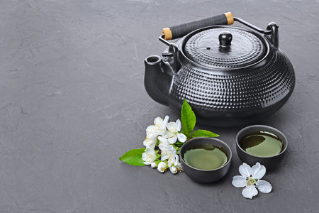 Asian black traditional teapot and teacups with green tea for ceremony on dark gray concrete background