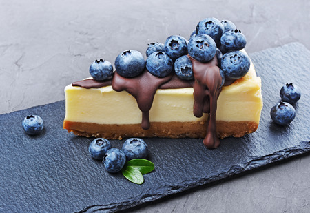 Close-up slice of delicious homemade cheesecake with fresh blueberries and chocolate cream on black slate board on gray concrete background