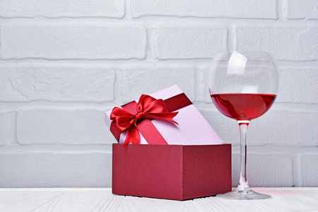 Glass with red wine for tasting and gift box for romantic surprise on gray brick wall background