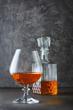 Strong alcoholic drink cognac in sniffer glass and crystal decanter on gray concrete background Foto de archivo