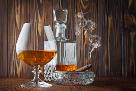 Strong alcoholic drink cognac in sniffer glass and decanter with smoking cigar in ashtray on wood texture background