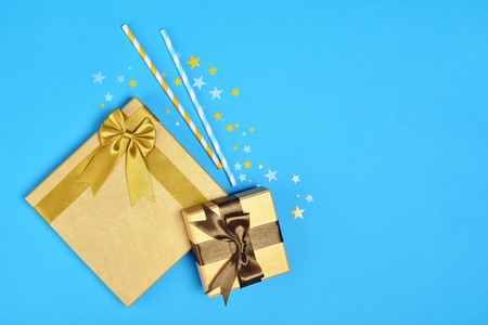 Golden shiny classic gift box with satin bow and cocktail straws with confetti in the shape of stars as attributes of party on blue background