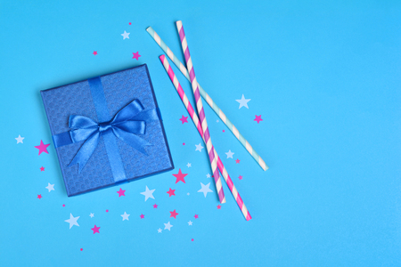 Shiny classic gift box with satin bow and cocktail straws with confetti in the shape of stars as attributes of party on blue background Stock Photo