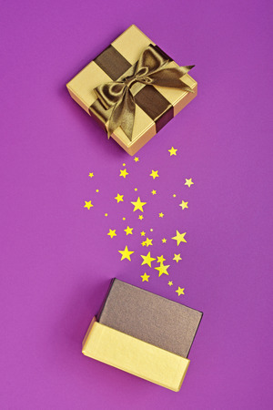 Opened shiny classic golden gift box with brown satin bow and magic confetti in the shape of stars as attributes of party on purple background